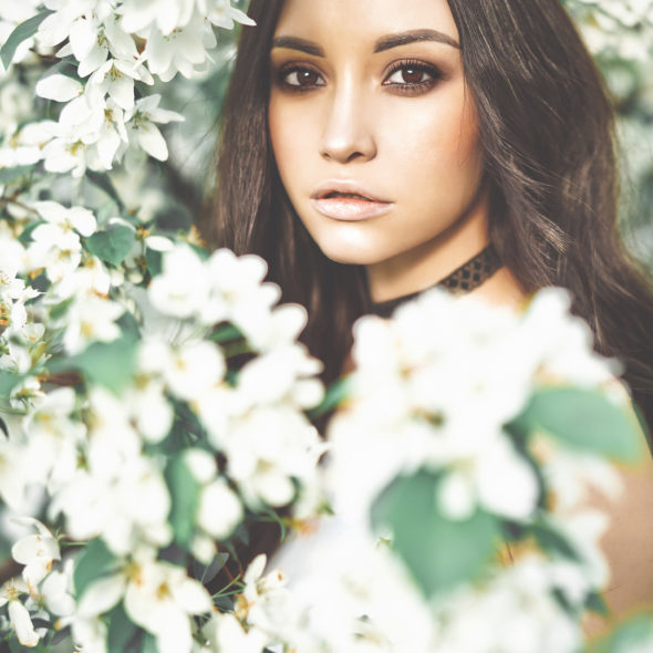 Outdoor fashion photo of beautiful young woman surrounded by flowers of apple-tree. Spring blossom. Summer vibes
